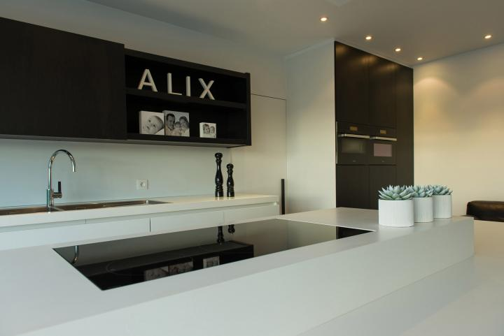 Strakke keuken met tablet en kookzone volledig in witte Corian.