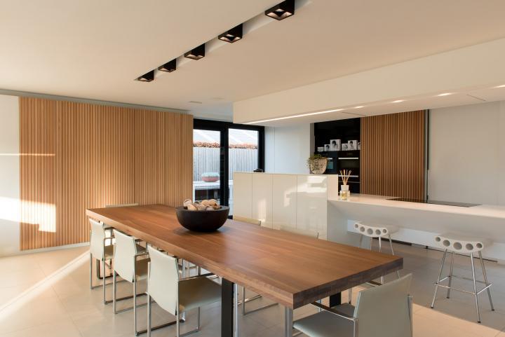 Hedendaags concept met gebruik van witte corian, witte hoogglans en warme houttinten.